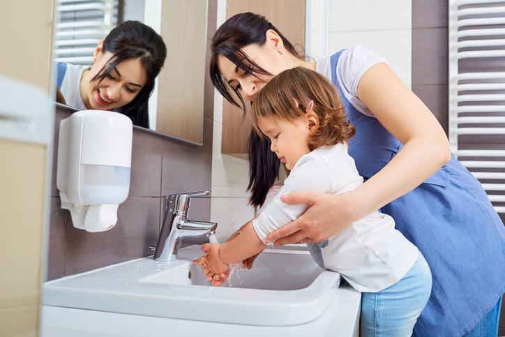 Kid washing hands with mom in the bathroom.