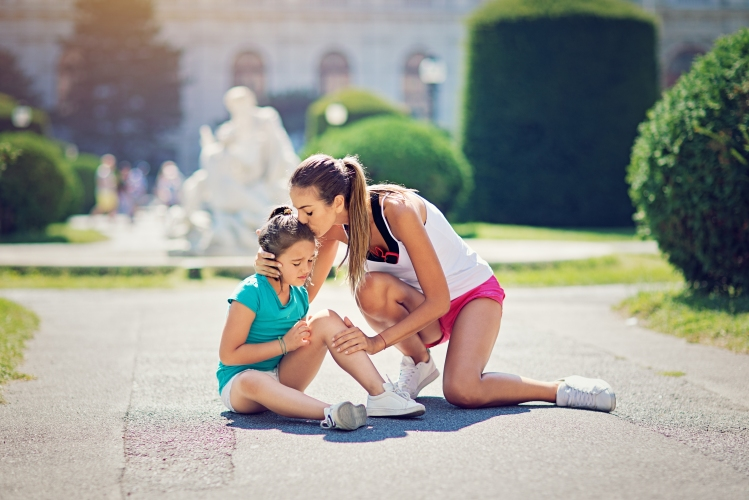Mother is hugging and kissing her injured runner daughter fallen on the ground