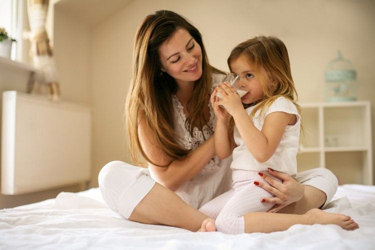 Mother with her daughter enjoying in bed together.